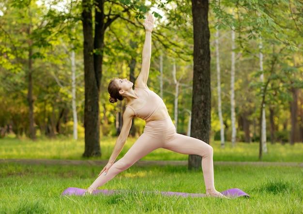 Кавказская девушка упражнениями йоги на природе
