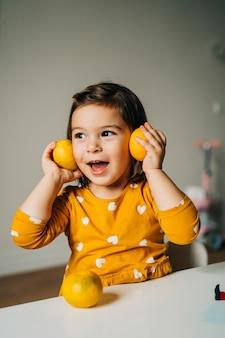 Кавказская девушка весело с мандаринами. здоровое детское питание. повышение иммунитета с помощью витамина с