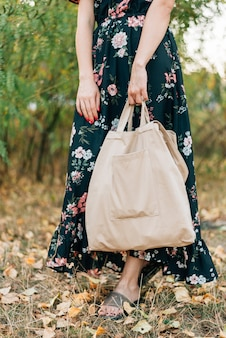 Caucasian girl holds linen shopper on sunset outdoors
