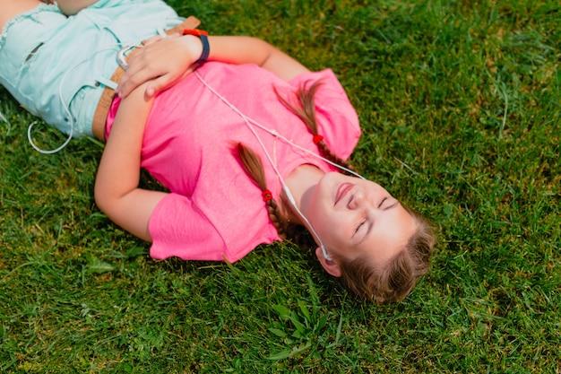 ピンクのtシャツと白いヘッドフォンで白人の女の子が音楽を聴きます。女子学生は緑の芝生に笑みを浮かべて横たわり、太陽の光に顔を向けます。