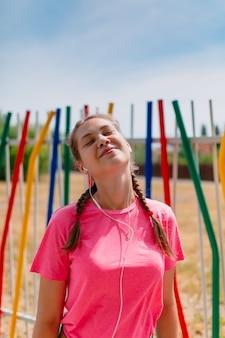ピンクのtシャツと白いヘッドフォンで白人の女の子が音楽を聴きます。女子学生は微笑み、顔を太陽光線にさらします。