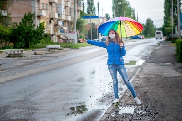 防護マスクの白人少女は、空の路上でタクシーを呼び止め、春の雨の中で傘を持って立って、車を待ちます。コロナウイルス大流行時の安全性と社会的距離。