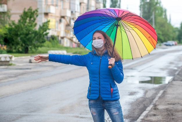 防護マスクの白人少女は、空の路上でタクシーを呼び止め、春の雨の中で傘を持って立って、車を待ちます。安全と社会的距離