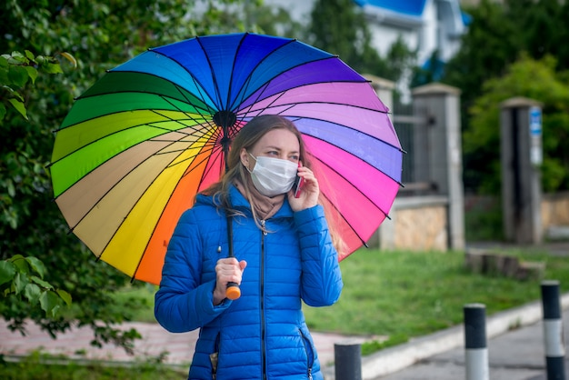 防護マスクの白人少女は、春の雨の傘の下のバス停で空の通りに立ち、電話で話します。