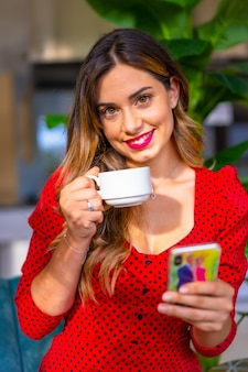 Кавказская девушка в красном платье за чашкой кофе