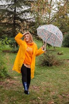 Кавказская девушка в желтом плаще гуляет на улице в дождливый день осенью люди осенью