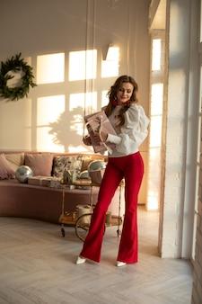 赤いズボンと白いシャツを着た白人の女の子は、大きな窓と笑顔の近くの彼女の部屋に贈り物を持っています