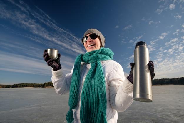 Кавказская девушка в солнцезащитных очках, белой куртке и голубом шарфе держит термос с кружкой и улыбается