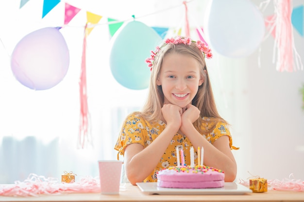 Caucasian girl is dreamily smiling and looking at birthday rainbow cake. festive colorful background with balloons. birthday party and wishes concept.