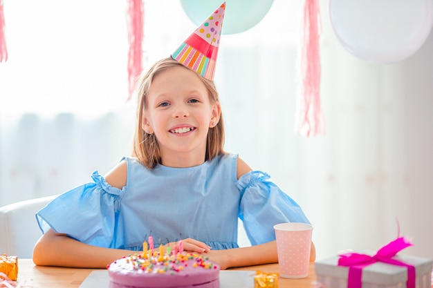 Caucasian girl is dreamily smiling and looking at birthday rainbow cake.
