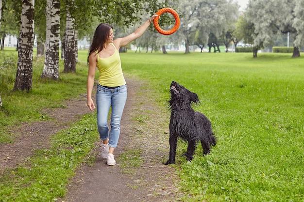 백인 소녀는 걷는 동안 검은 briard 점프를 훈련하기 위해 장난감을 사용하고 있습니다.