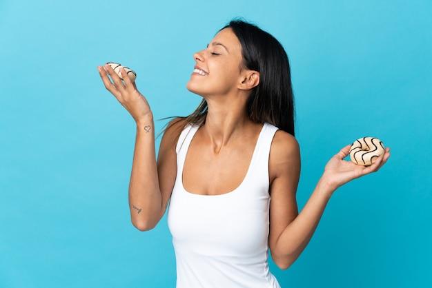 幸せな表情で青い保持ドーナツに分離された白人の女の子