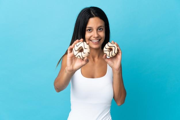 幸せな表情でドーナツを保持している青い壁に分離された白人の女の子