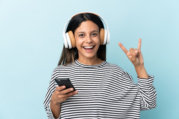 Кавказская девушка изолирована на синей стене, слушая музыку с мобильным телефоном, делая рок-жест