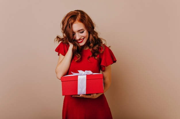 Caucasian girl looking at birthday present with smile. charming ginger lady holding new year gift.