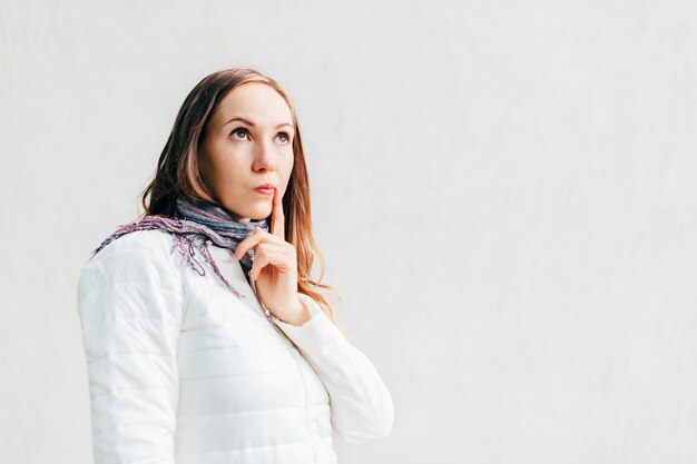 Caucasian girl looks away thoughtfully putting finger to the corner of her mouth.