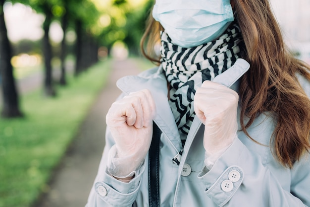 Caucasian girl in a medical mask and a gray coat walks in the park