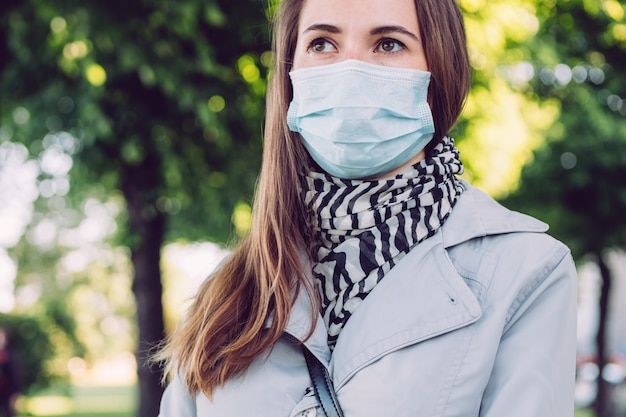 Caucasian girl in a medical mask walks in the park
