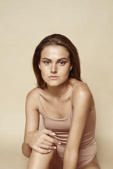 Кавказская девушка модель со свежей сияющей увлажненной кожей лица на бежевом