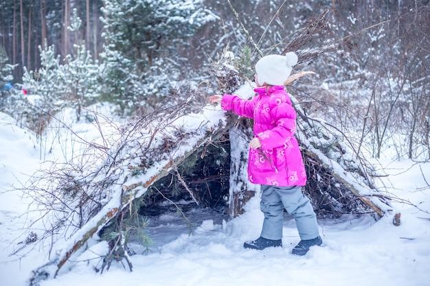 5歳の白人の女の子が冬の森の針葉樹の枝から小屋を建て、冬に屋外で遊ぶ