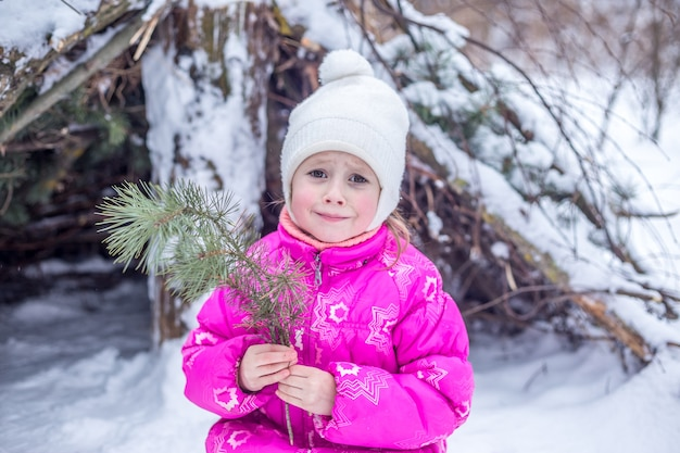 冬の森で遊んで、冬に屋外で過ごす5歳の白人少女