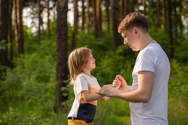 Кавказская девочка 6 лет держит папу за руку, глядя друг на друга в лесу. отец и дочь играют вместе, смеются и веселятся. концепция деятельности счастливой семьи