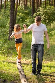 Кавказская девочка 6 лет идет по бревну, держа за руку папу. отец и дочь играют вместе, смеются и веселятся. концепция деятельности счастливой семьи