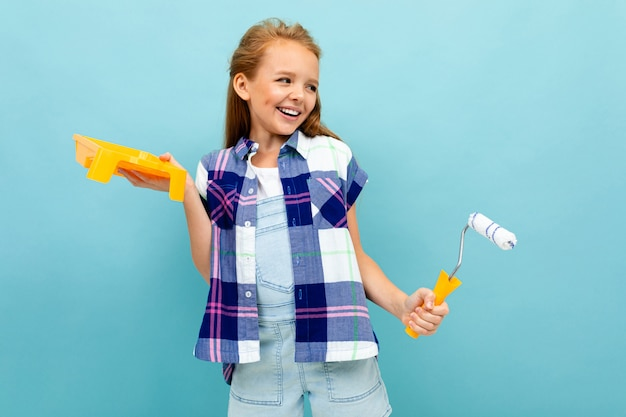 Caucasian girl paints a wall with a roller and paint isolated on blue
