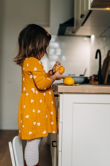 Caucasian girl peeling tangerines on kitchen counter. healthy child diet. immune boosting with vitamin c. high quality photo