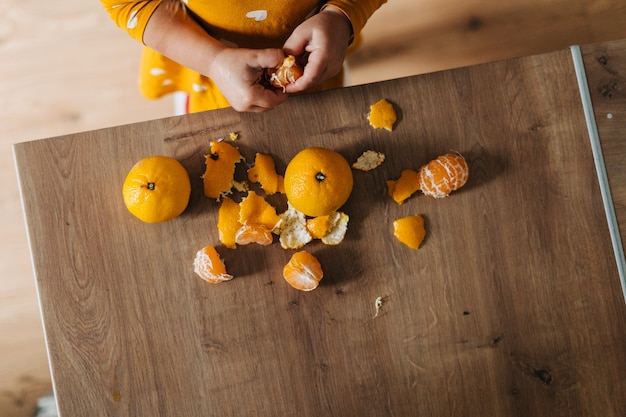 Caucasian girl peeling tangerines on kitchen counter. healthy child diet. immune boosting with