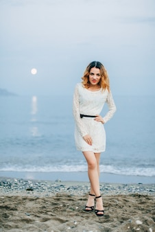 Caucasian girl posing by the sea on the beach in the evening