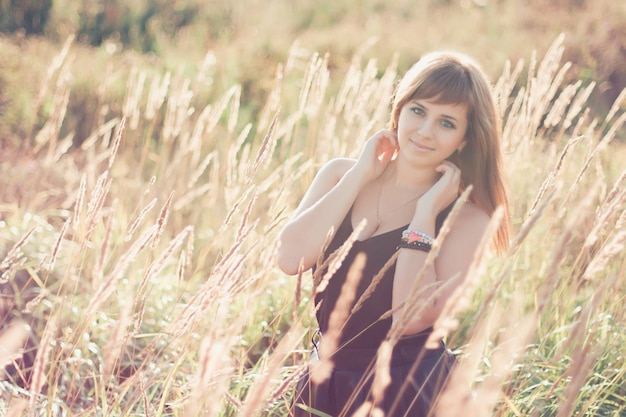 Caucasian girl posing in summer at sunset in the field