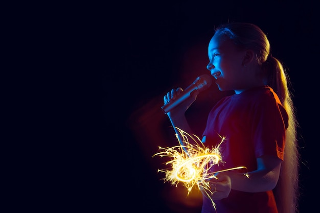 Caucasian girl's portrait on dark studio background in neon light. beautiful female model with speaker and sparkler.