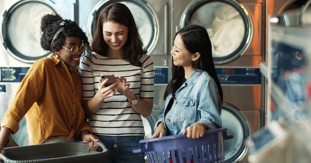 Кавказская девушка показывает фотографии на смартфоне подруг смешанной расы во время работы стиральных машин и чистки одежды. многонациональные женщины смотря видео на телефоне в прачечной.