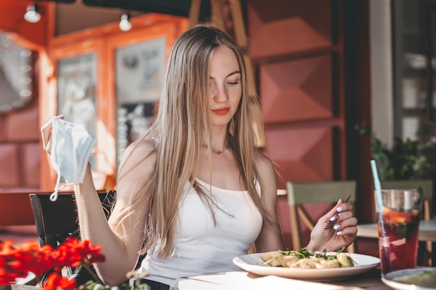 Caucasian girl sits at a table in a cafe, takes off her protective medical face mask