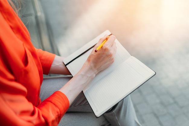 백인 소녀는 도시에 앉아서 노트북에 메모를 합니다.