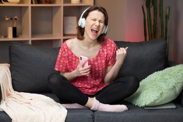 白人の女の子が家のソファーに座っていると、笑みを浮かべて、現代のスマートフォンのヘッドフォンで音楽を聴きます。