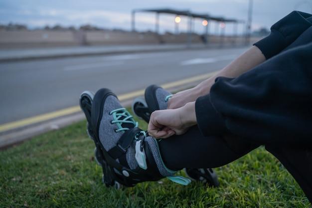 遊歩道で日没時に彼女のスケート靴を結ぶ草の上に座っている白人の女の子