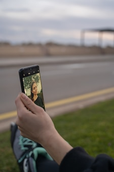 スマートフォンを見て、日没で笑顔でスケートと草の上に座っている白人の女の子