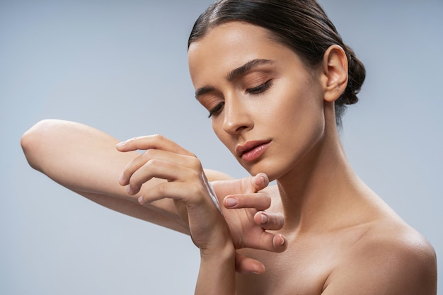 Кавказская девушка, пахнущая ароматом под рукой на светлом фоне