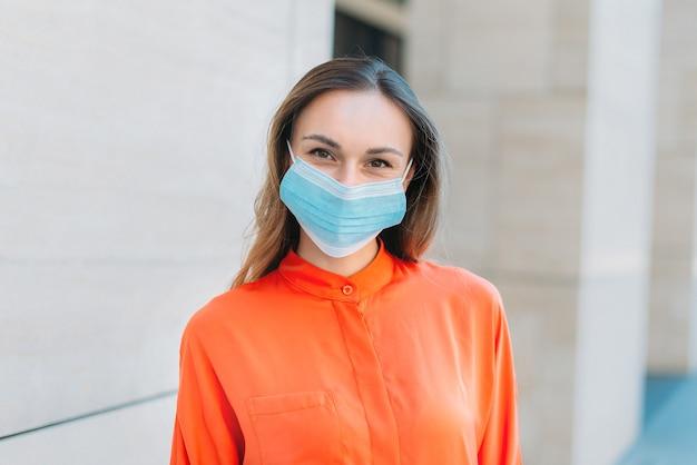 夏の街を歩いて笑顔と医療マスクを身に着けている白人の女の子