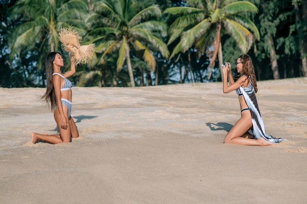 Caucasian girl takes pictures of his asian girlfriend in a bikini and straw hat on the beach. tropical resort. vacation with friends.