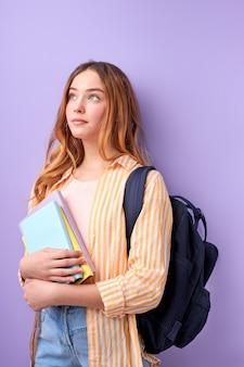 バックパックと紫で隔離の本とカジュアルな服装の白人少女10代の学生