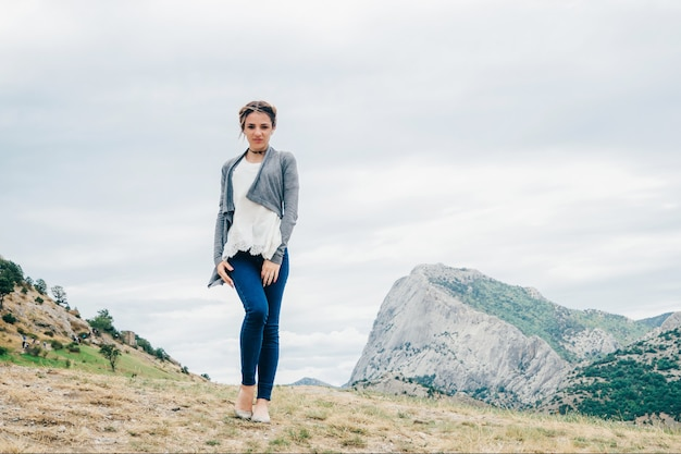 Caucasian girl traveler stands on the top of a mountain