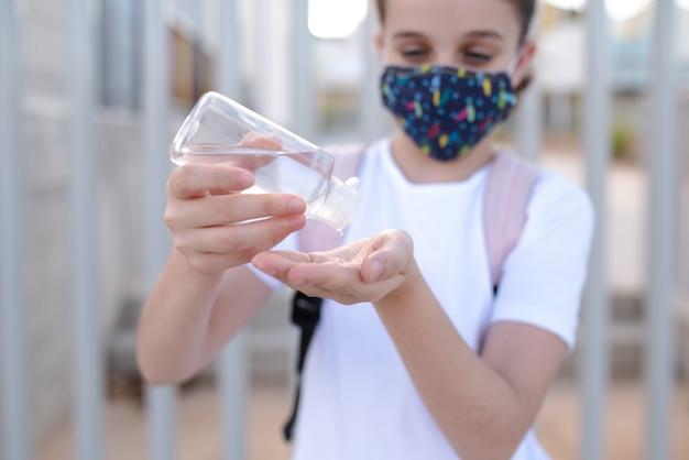 新しい通常の学校のドアで彼女の手にアルコールを注ぐマスクを着ている白人の女の子