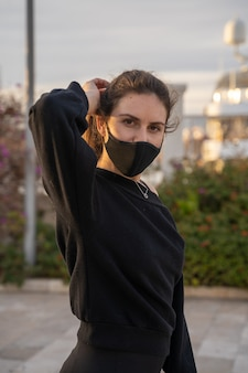 Caucasian girl wearing a mask looking at the camera while wearing roller skates