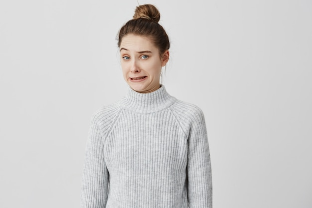 Caucasian girl with brown hair in bun posing with facial expressions of disgust. female 20s making face meaning dislike and non-acceptance. human reactions concept