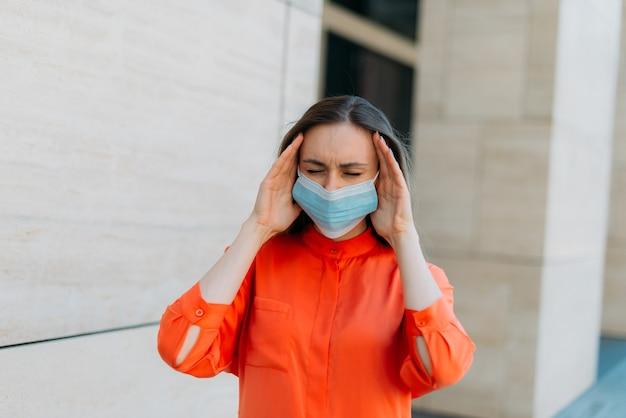 Кавказская девушка с закрытыми глазами в медицинской маске с головной болью