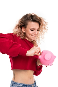 Caucasian girl with curly fair hair trying to get money from the pink pig moneybox, portrait isolated on white