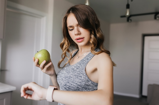 Caucasian girl with elegant hairstyle looking at her watch. indoor shot of beautiful white lady with apple in hand.